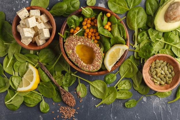 Gezonde vegetarische salade met tofu, kikkererwten, avocado en zonnebloempitten. gezond veganistisch eten concept. donkere achtergrond, bovenaanzicht, kopie ruimte.