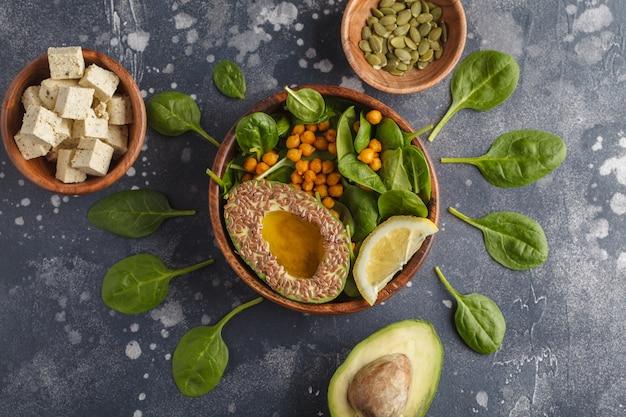 Gezonde vegetarische salade met tofu, kikkererwten, avocado en zonnebloempitten.