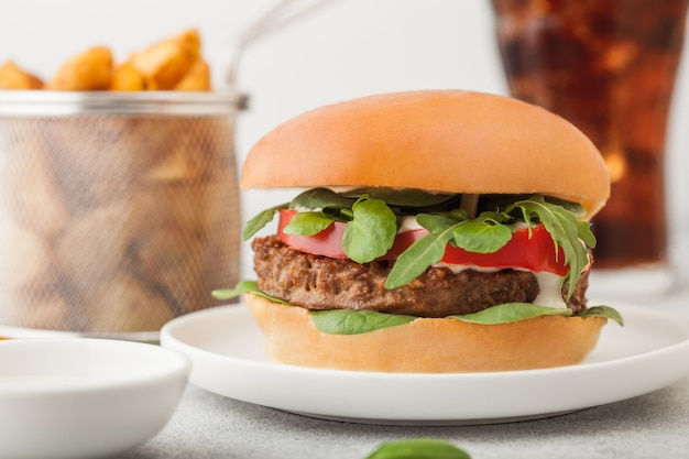 Gezonde vegetarische vleesvrije hamburger op ronde keramische plaat met groenten op lichte achtergrond met aardappelpartjes en glas cola.