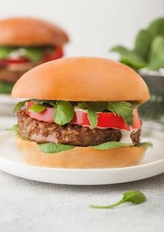 Gezonde vegetarische vleesvrije hamburgers op ronde keramische plaat met groenten en spinazie op lichte achtergrond. detailopname