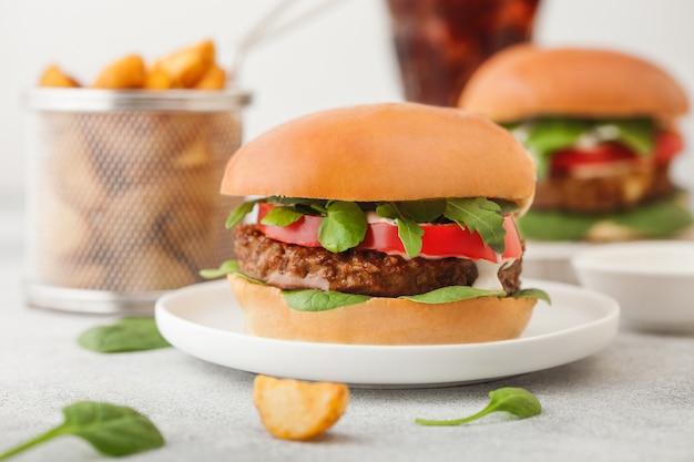 Gezonde vegetarische vleesvrije hamburgers op ronde keramische plaat met groenten op lichte achtergrond met aardappelpartjes en glas cola.