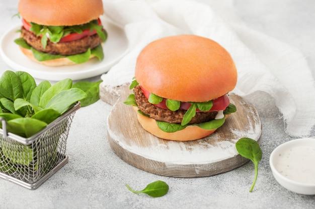 Gezonde vegetarische vleesvrije hamburgers op ronde snijplank met groenten en spinazie op lichte achtergrond.
