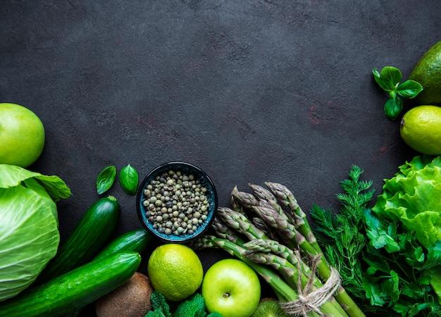 Gezonde vegetarische voedselconceptenachtergrond, verse groene voedselselectie voor detoxdieet op een zwarte concrete achtergrond