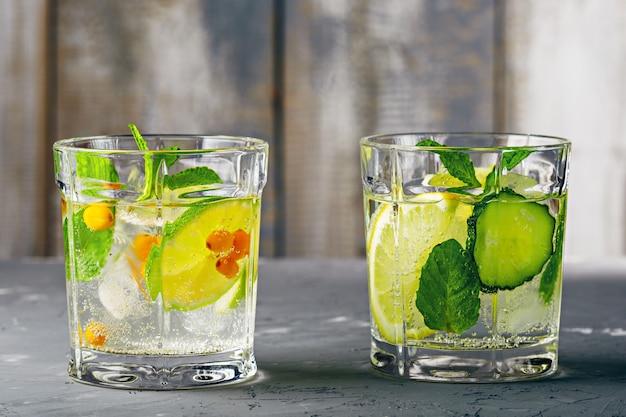 Gezonde verfrissende cocktail met citroen, limoen, duindoorn, komkommer en munt op grijze houten tafel
