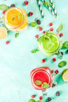 Gezonde vers fruit en veggie smoothies met ingrediënten op lichtblauwe concrete lijst, exemplaar ruimte hoogste mening