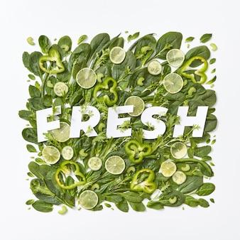 Gezonde verscheidenheid aan groene groenten kool, spinazie, bloemblaadjes, stukjes asperges peper op een grijze achtergrond met een papieren inscriptie vers op een grijze achtergrond met kopie ruimte. plat leggen