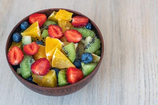 Gezonde verse fruitsalade in kom op licht.