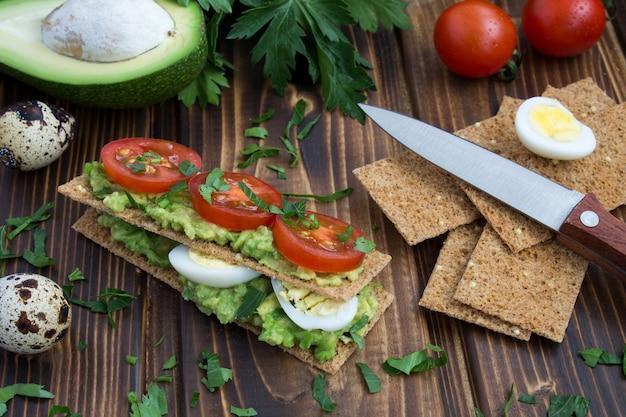 Gezonde voeding: beschuit met kwarteleitjes, avocado en kers op de houten achtergrond