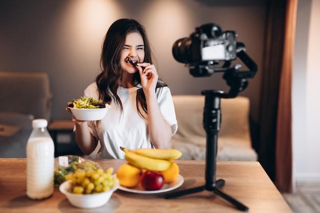 Gezonde voeding blogger jonge vrouw verse veganistische salade eten in keuken studio, film tutorial op camera voor videokanaal. vrouwelijke influencer laat geen junkfood zien, praat over gezond eten.