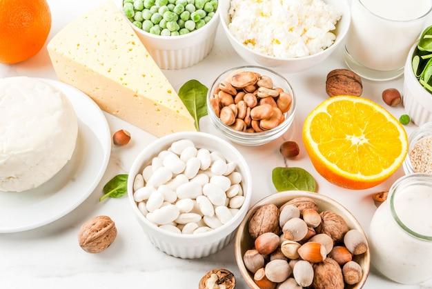 Gezonde voeding concept. set van voedsel rijk aan calcium - zuivel en veganistische ca producten witte marmeren achtergrond