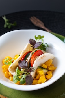 Gezonde voeding concept vegan microgreen salade tacos sandwich in witte keramische kom op zwart mat met kopie ruimte