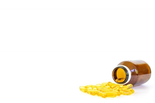 Gezonde voeding concept vis oliecapsules met omega-3 en vitamine d-overloop vormen een glazen fles geïsoleerd
