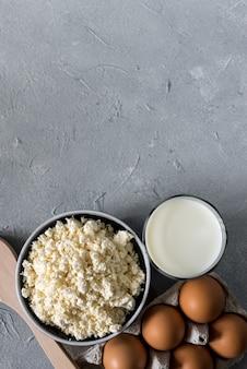 Gezonde voeding concept, zelfgemaakte kwark, een glas melk, yoghurt en kippeneieren op een stenen achtergrond, zuivelproducten