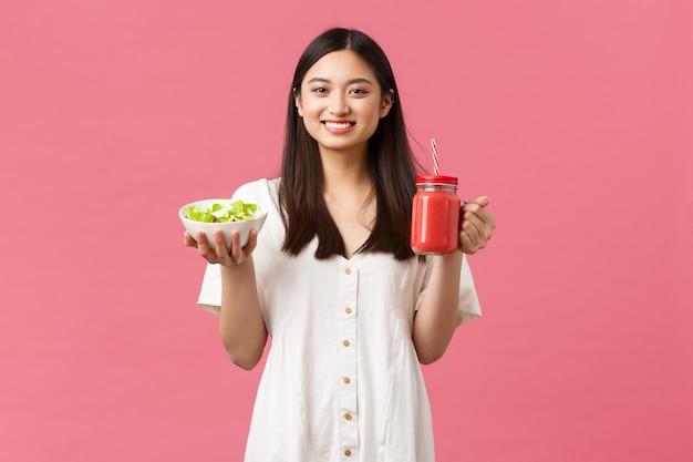 Gezonde voeding, emoties en zomer lifestyle concept. enthousiast en vrolijk schattig aziatisch meisje vol energie, smakelijke frisse salade eten en smoothie drinken, glimlachend in de camera gelukkig, roze achtergrond