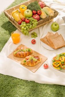 Gezonde voeding en accessoires buiten zomer of lente picknick, picknick rieten mand met vers fruit, brood en een glas verfrissende jus d'orange op de camping natuur achtergrond.
