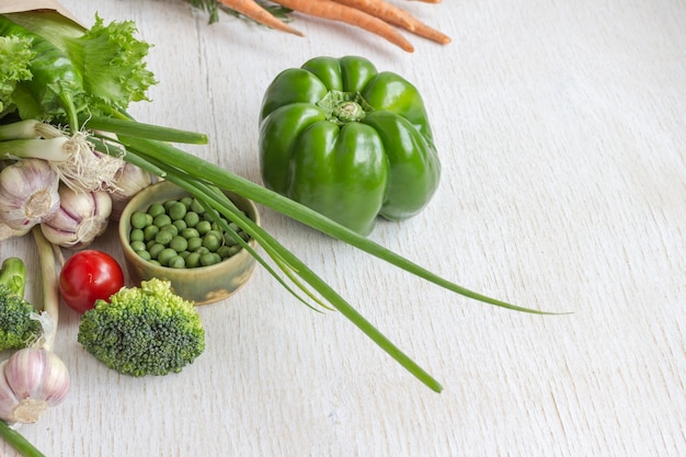 Gezonde voeding in een papieren zak met verschillende groenten op witte tafel. bovenaanzicht