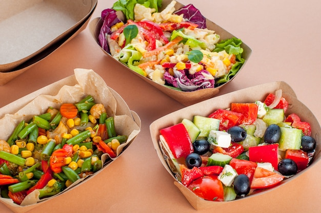 Gezonde voeding in een wegwerp milieuvriendelijke voedselverpakking. groentesalades in de voedselcontainers van bruin kraftpapier op beige oppervlak.