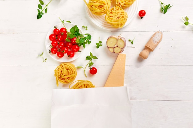 Gezonde voeding in papieren boodschappentas, ingrediënten voor het koken van italiaanse pasta op witte ondergrond, shopping food supermarkt concept, gezond eten, koken diner concept. kopieer ruimte