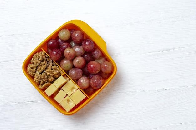 Gezonde voeding in plastic bak klaar om te eten met kaas, druiven en walnoten op tafel