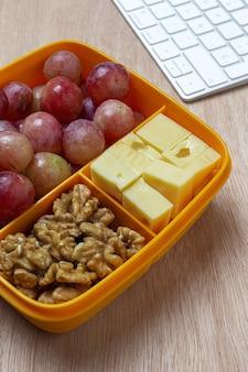 Gezonde voeding in plastic bakjes klaar om te eten met kaas, druiven en walnoten op de werktafel.