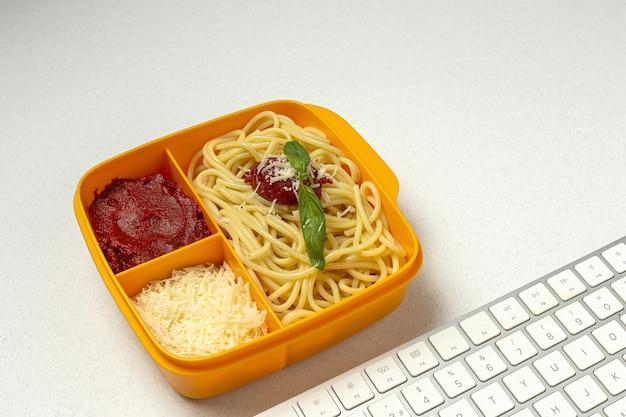 Gezonde voeding in plastic bakjes klaar om te eten met zelfgemaakte spaghetti met tomaat, kaas en basilicum op de werktafel. italiaans eten. wegnemen.