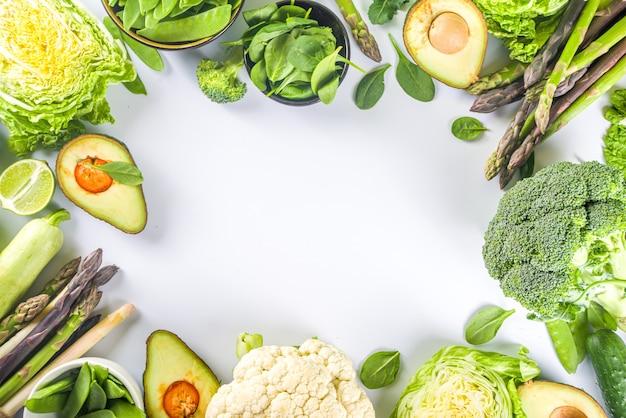 Gezonde voeding lente voedsel achtergrond. assortiment van verse rauwe biologische groene groenten - broccoli, bloemkool, courgette, komkommers, asperges, spinazie, avocado, kool ingesteld op witte achtergrond