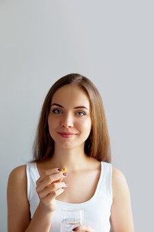 Gezonde voeding. portret van mooie glimlachende jonge vrouw vitamine pil te nemen