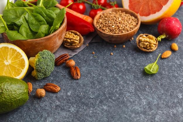 Gezonde voeding, trendy alkalische dieetproducten - fruit, groenten, granen, noten, olie, donkere tafel, kopie ruimte