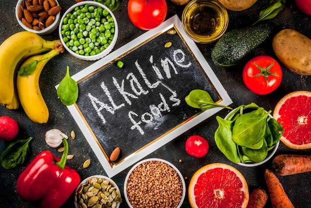 Gezonde voedingsachtergrond, trendy alkalische dieetproducten - fruit, groenten, granen, noten. oliën, donkerblauwe betonnen achtergrond hierboven