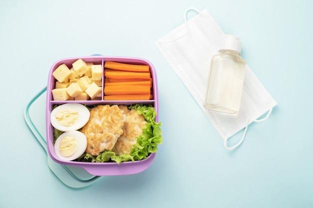 Gezonde voedsel plastic lunchcontainer. een medisch gezichtsmasker en een fles ontsmettingsmiddel zijn in de buurt.