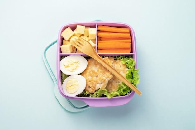 Gezonde voedsel plastic lunchcontainer met inbegrip van kippenkoteletten, kippenei, salade, wortelwiggen, kaasplakken. blauwe achtergrond