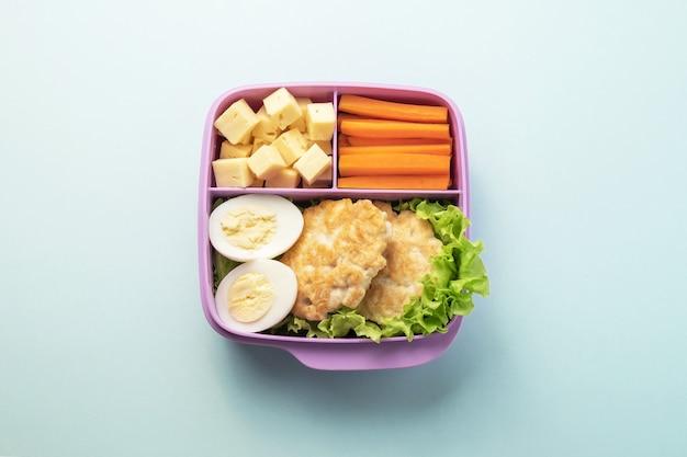 Gezonde voedsel plastic lunchcontainer met inbegrip van kippenkoteletten, kippenei, salade, wortelwiggen, kaasplakken.