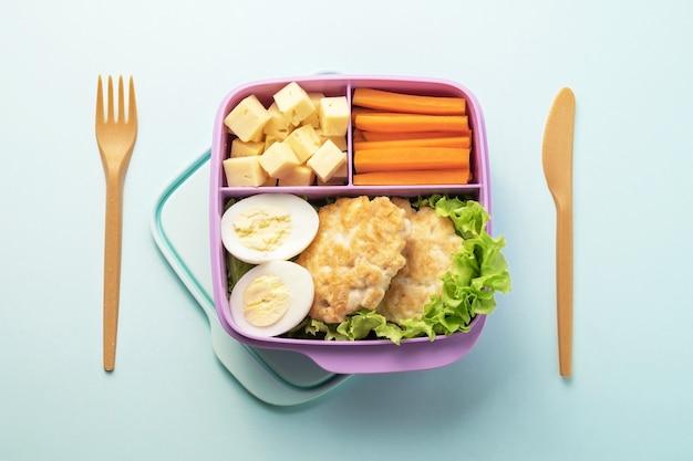 Gezonde voedsel plastic lunchcontainer. vork en mes op blauwe achtergrond