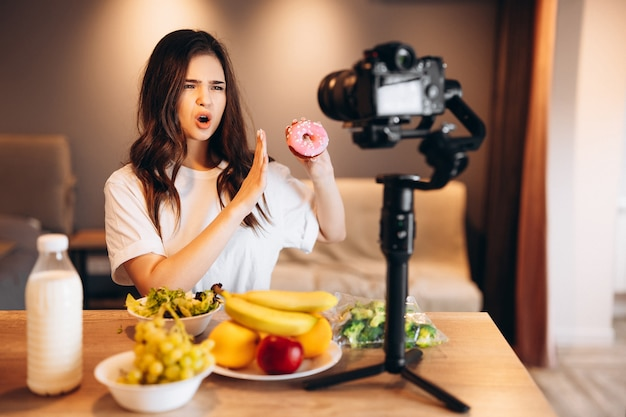 Gezonde voedselblogger jonge vrouw die verse veganistische fruitsalade kookt en nee zegt tegen snoep in de keukenstudio filmt tutorial op camera voor videokanaal vrouwelijke influencer laat geen junkfood zien