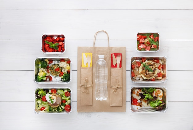Gezonde voedsellevering. afhaalmaaltijden. groenten, vlees en fruit in foliedozen, bestek, water en pakpapier. bovenaanzicht, plat lag op wit hout met kopie ruimte