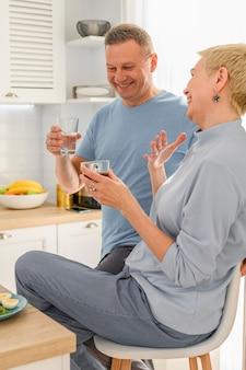 Gezonde volwassen geniet van koffieontbijt samen zittend op een keuken glimlachend praten en lachen