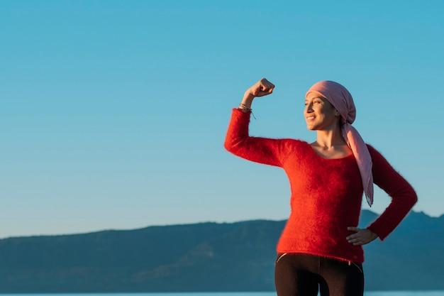 Gezonde vrouw die haar vuist van macht toont tegen vrouwelijke kanker op de achtergrond van de blauwe hemel. ze draagt een roze sjaal en een rode trui.