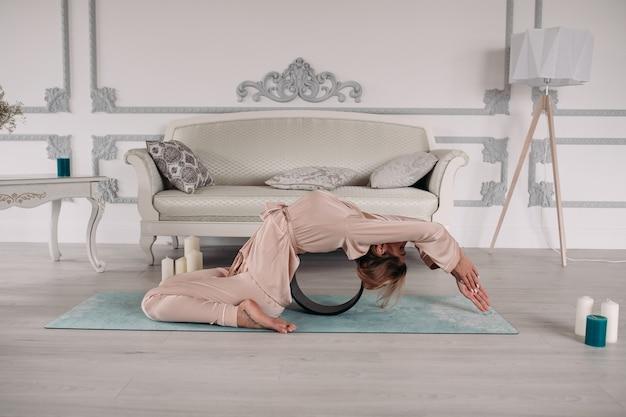 Gezonde vrouw in roze pyjama die haar ochtend begint met yoga en ontspanning op de yogamat bij de grijze bank