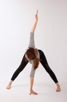 Gezonde vrouw in zwarte sportenleggings die zich op een wit geïsoleerde achtergrond uitrekken. yoga dag