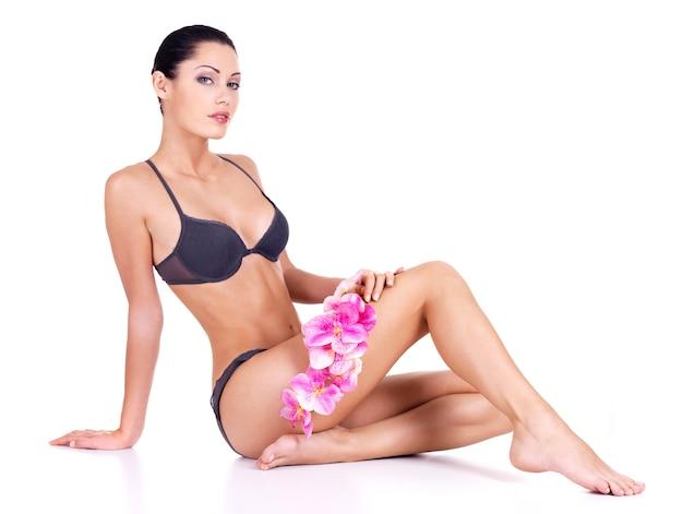 Gezonde vrouw met mooie lange slanke benen in ondergoed zit op witte muur