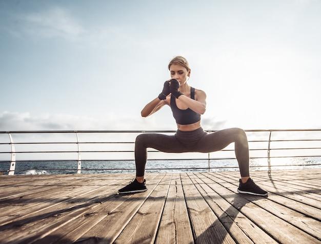 Gezonde vrouw training op boulevard jonge aantrekkelijke vrouw in sportkleding doet squats oefenen op het strand bij zonsopgang