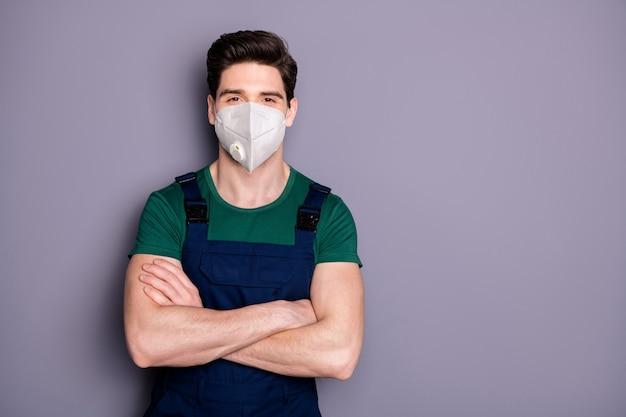 Gezonde werkman draagt veiligheidsademhalingsmasker mers griepinfectiepreventie gevouwen armen