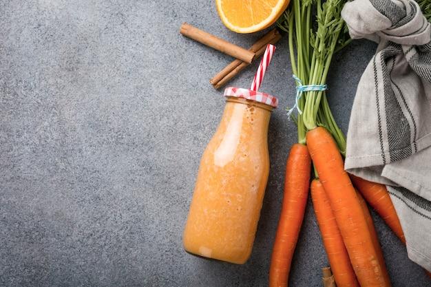 Gezonde wortel smoothie met sinaasappel en kaneel in glazen fles en ingrediënten.