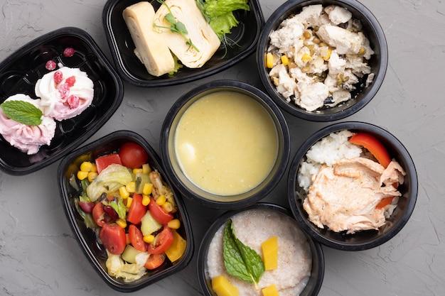 Gezonde zakelijke lunchboxen grijze tafel. groenten en gebakken kip lunchbox op bureau, bovenaanzicht