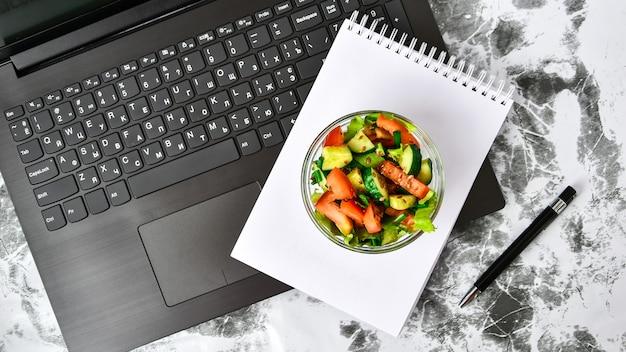 Gezonde zakenlunch snack in kantoor, groentesalade, leeg notitieboekje met pen