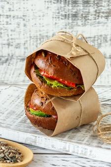 Gezonde zalmburger met avocado en tomaat geserveerd in ambachtelijk papier op houten ondergrond.