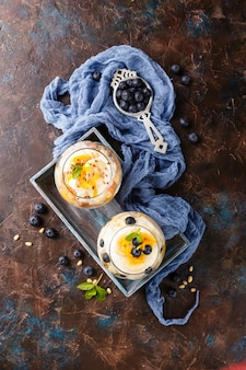 Gezonde zelfgemaakte gelaagde dessert kleinigheid met sinaasappel, bosbessen, koekje, yoghurt en granola in glazen in houten kist. bovenaanzicht