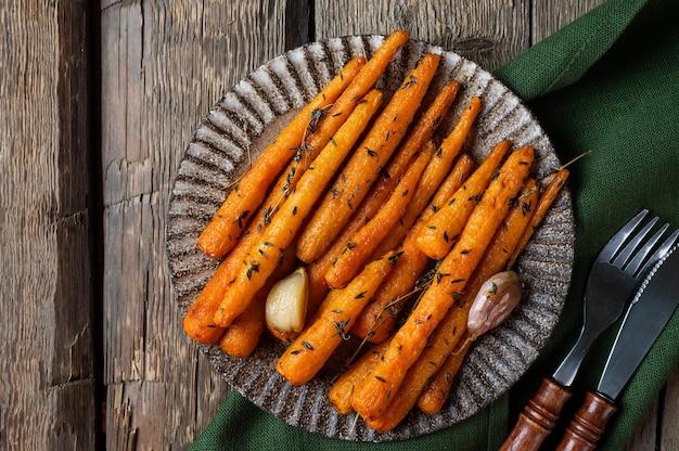 Gezonde zelfgemaakte geroosterde wortelen klaar om te eten. geglazuurde wortel met kruiden en knoflook bovenaanzicht. gebakken wortel op houten achtergrond. gebakken groenten. troosteten.