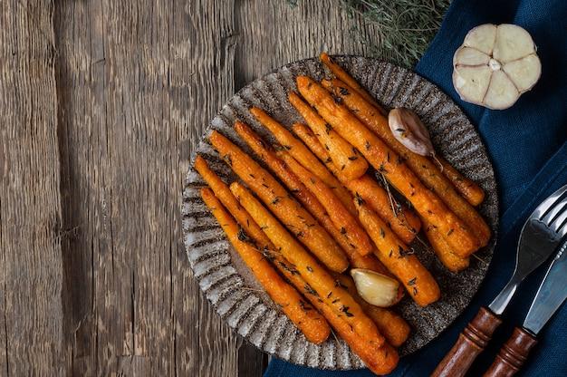 Gezonde zelfgemaakte geroosterde wortelen klaar om te eten. geglazuurde wortel met kruiden en knoflook. gebakken wortel op houten achtergrond. gebakken groenten. troosteten.