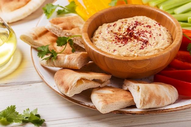 Gezonde zelfgemaakte hummus met diverse verse groenten en pitabroodje.